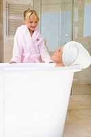 Young woman lying in bath, towel on head, smiling up at daughter 6-8