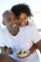 Young couple embracing, smiling, portrait, woman holding fruit salad