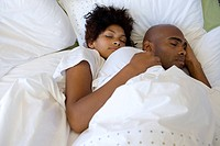 Young couple asleep in bed, elevated view (thumbnail)