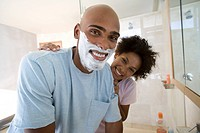 Young couple in bathroom, man with shaving foam on face, smiling, portrait