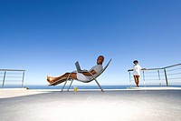 Young man sitting with laptop on deck chair by sea, side view, woman in background, smiling, portrait