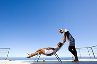 Young man standing by young woman lying on deck chair by sea, smiling at each other, side view