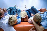 Family of four sitting on sofa with popcorn, elevated view