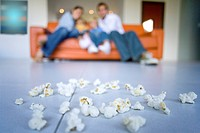 Family of four sitting on sofa, focus on popcorn in foreground, low angle view
