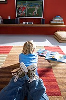 Girl 6-8 lying on rug in front of television, rear view