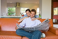Woman embracing man sitting on sofa with newspaper, smiling