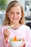 Girl 6-8 holding up piece of cucumber from bowl, smiling, portrait