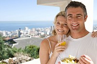 Couple standing on balcony with breakfast, smiling, portrait