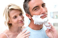 Woman embracing man in bathroom, man putting shaving foam on face, smiling, portrait, close-up