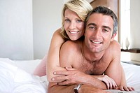 Couple embracing on bed, smiling, portrait