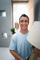 Man holding lamp, woman holding pot plant, smiling, portrait