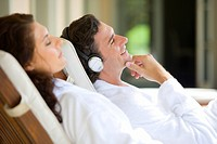 Couple relaxaing on deck chairs, man wearing headphones, smiling, side view