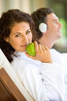 Couple relaxing on deck chairs, portrait of woman holding green apple, smiling