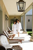 Couple wearing white robes, walking on verandah smiling