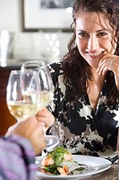 Couple toasting white wine glasses, woman smiling, close-up