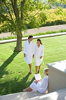 Couple wearing white robes, holding hands whilst walking in garden by woman, elevated view
