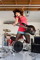 Teenage girl 15-17 playing electric guitar in garage, jumping in air