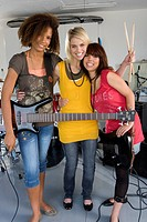 Three teenage girls 15-17 in garage band, smiling, portrait