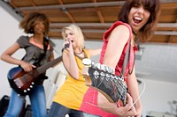 Three teenage girls 15-17 in garage band, teenage girl playing electric guitar in foreground
