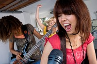 Three teenage girls 15-17 in garage band, teenage girl singing in foreground