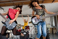 Three teenage girls 15-17 in garage band, two girls playing electric guitar in foreground