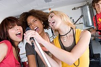 Three teenage girls 15-17 singing in garage band