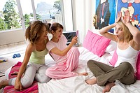 Three teenage girls 15-17 sitting on bed, one taking photo with camera phone other friend pulling face