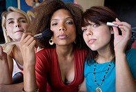 Three teenage girls 15-17 applying make-up, close-up
