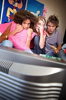 Three teenage friends 15-17 watching television with scared expressions on faces, television in foreground