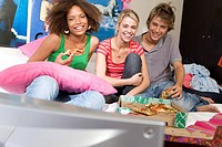Three teenage friends 15-17 watching television in bedroom, smiling, television in foreground