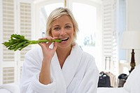 Woman wearing white bath robe, biting on celery, smiling, portrait