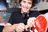 Young man in bedroom with skateboard, smiling, portrait, close-up