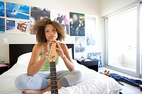 Teenage girl 16-18 sitting on bed with electric guitar, portrait