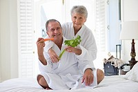 Senior couple in bedroom holding celery and carrot sticks, smiling, portrait