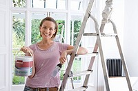 20's woman home decorating indoors with paint, brush and ladder