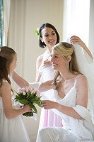 30´s bride indoors being attended to by bridesmaids, one holding bouquet,