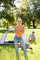 Young couple assembling dome tent on camping trip in woodland clearing, focus on woman, portrait