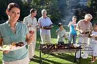 Three generation family standing beside barbecue grill in garden, focus on woman holding plate of food and glass of wine in foreground, smiling, portr...