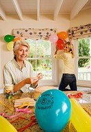 Senior woman and adult daughter preparing birthday party at home, mother placing candles on cake, daughter putting up balloons, smiling, portrait