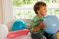Boy 4-6 sitting on window seat at home, holding blue party balloon, smiling, side view
