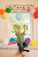 Boy 4-6 sitting on window seat at home, catching falling party balloon, arms up, smiling, front view