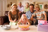 Three generation family sitting on sofa at home, girl 4-6 blowing out candles on birthday cake