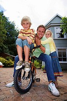 Father sitting on bicycle with children 4-6 in driveway, smiling, front view, portrait