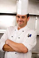 Male chef standing in commercial kitchen, arms folded, smiling, portrait