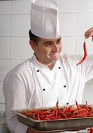 Male chef carrying full tray of red chilli peppers in commercial kitchen, examining single chilli, smiling