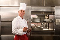 Mature male chef writing on clipboard in commercial kitchen, side view, portrait (thumbnail)
