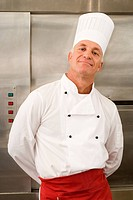 Mature male chef standing in commercial kitchen, hands behind back, smiling, front view, portrait