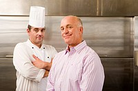Male chef and restaurant manager standing in commercial kitchen, smiling, portrait
