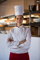 Confident female chef standing in commercial kitchen, arms folded, smiling, front view, portrait