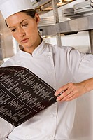 Female chef standing in commercial kitchen, looking at menu, close-up
